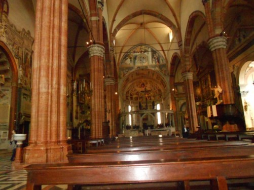 Inside Verona Cathedral. Looking across rows of seats towards the altar.