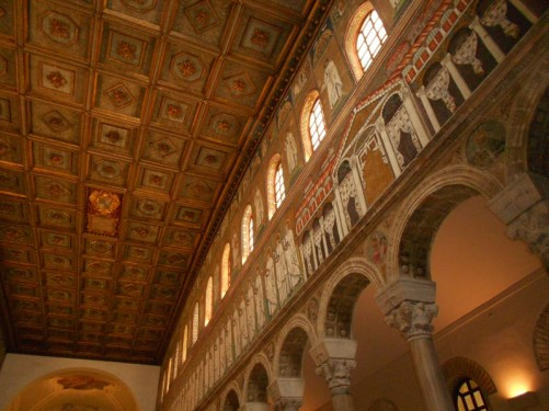 Looking up at mosaic decoration on the upper wall of the nave and the carved wooden ceiling.