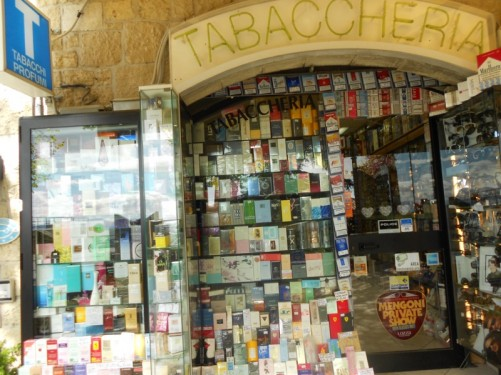 Outside a tobacconist's shop - hundreds of different cigarette packets displayed in the window.