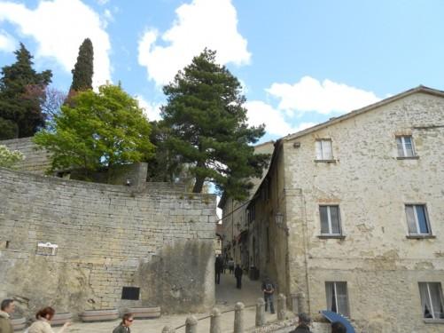 Outside the basilica. Tourists heading up a steep, narrow street.