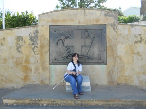 Tatiana sitting in front of the War Memorial of the Spetses Navy. There is a plaque with an emblem containing a cross, anchor, snake and owl, plus the words 'Freedom or death' in Greek.