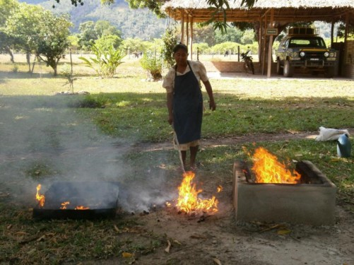 The woman has emptied the burning peanuts on to the ground and is spreading them out with the stick.
