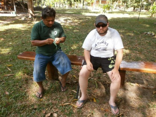 Tony sitting with an Amerindian man eating roast peanuts.
