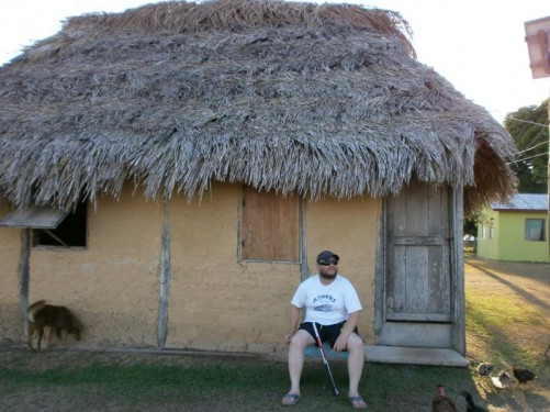 Tony sitting outside a hut with a thatched roof. A dog and some guinea fowl also in view.