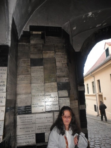 Tatiana inside the Stone Gate. The gate, which is actually more of a short tunnel, contains a shrine where an icon of the Virgin Mary is displayed inside a niche protected by a metal grill. The icon is believed to have miraculous powers, apparently due to it surviving a fire in 1731 perfectly preserved. Behind Tatiana is a wall covered with stone plaques. These contain messages of thanks from people whose prayers have been answered.
