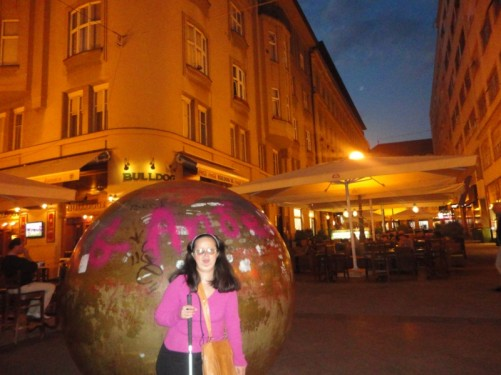 Tatiana by a large smooth granite ball - a street artwork known as 'The Grounded Sun'.