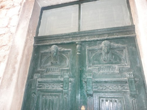 Decorative metal doorway in the old town. Double doors with moulded heads at the top of each.