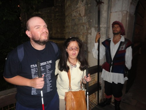 Tony and Tatiana at Pile Gate. There is a man dressed as an old-style guard at the side.