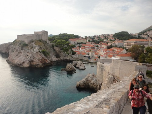 Tony and Tatiana together with other tourists climbing up steps on the route around part of the city walls. A small harbour below with Bokar Fort at the far side.