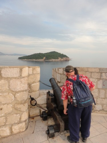 By a canon on the walls. View in the distance of the tree-covered island of Lokrum, a 15-minute boat ride from the harbour in the old town.
