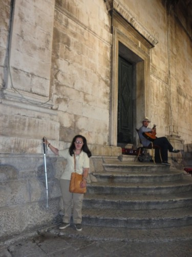 Tatiana at the side of St Blaise's Church. Behind a man is sitting atop some steps playing a guitar.