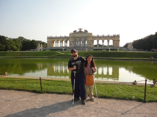 Tony and Tatiana in front of a lake. Behind the lake is the Gloriette, a large arcaded structure built in 1775. This stands on top of Schönbrunn Hill, some 60 metres (200 feet) above the palace itself. The Gloriette today houses a café and provides excellent views across the city.