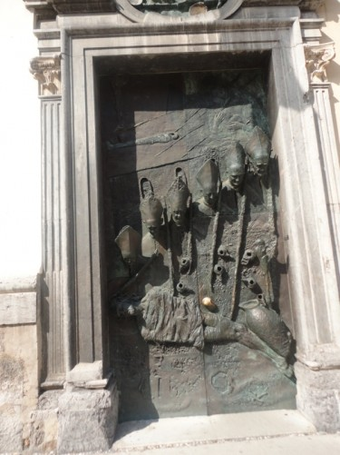 The City Door (or Ljubljana Door) into the cathedral. This heavy bronze door contains busts of various bishops of the city. It was sculpted by Mirsad Begic in 1996.