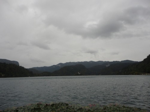 The shore of Lake Bled. A cloudy and wet day. Away in the distance the Church of the Assumption can just be seen on Bled Island in the lake.