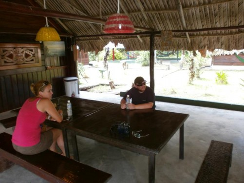 Tony with a female traveller from the Netherlands sitting at a table under the shelter. This building is the dining room of the eco-lodge near the Maroon village. The area is only a two hour drive from Paramaribo.