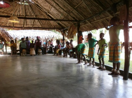A group of Maroon villagers, some with traditional drums, and lots of children, under the dining room of the eco-lodge near the Maroon village.