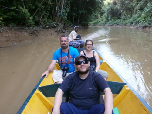 Tony in the canoe. Muddy river with dense jungle vegetation on both sides. This is the beginning of Suriname's interior.