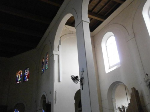 Looking to the side of the main altar. Plain design with white painted walls, but colourful stained glass in the windows.