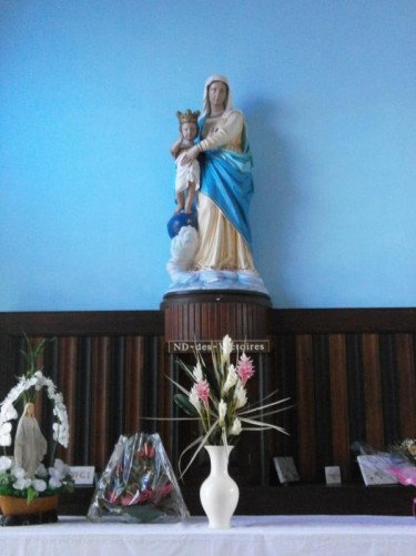 Small statue of the Virgin Mary with baby Jesus on a side altar.