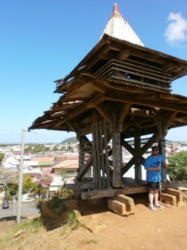 Tony in front of a wooden lookout tower at Fort Cépérou. Buildings and streets of the town can be seen below.