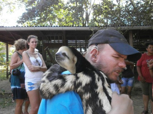 Tony holding a sloth. The sloth resting its arm on Tony's shoulder.