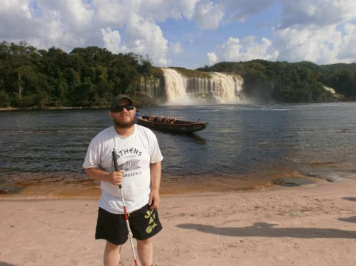 Tony standing on a sandy beach with another beautiful shot of Salto Hacha away on the opposite side of the lagoon. The canoe waiting nearby. The beach is on Isla Anatoly – a sand island in Canaima Lagoon.