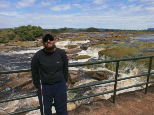 Back near Canaima Village. Tony by railings overlooking the fast-flowing rocky Carrao River.