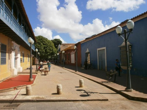 Looking along Paseo Talavera, a pedestrian colonial-era street. The colonial buildings that line the street include the Coro Art Museum. In front workmen are repaving part of the street.