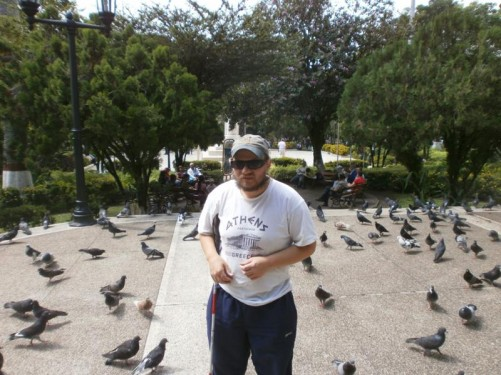 Tony standing among pigeons in Plaza Bolivar.