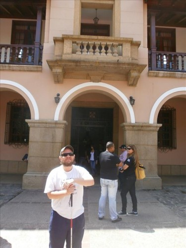 The main doorway into a colonial-era building located near the plaza. A stone balcony above. Possibly a government building.