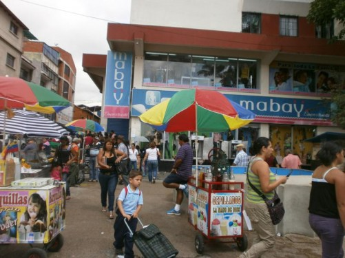 Busy street scene. Several small stalls selling drinks and snacks.