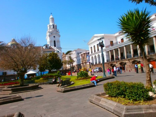 View across the square towards Quito's cathedral. The cathedral's exterior is painted white with a tower at one end and a dome in the middle.