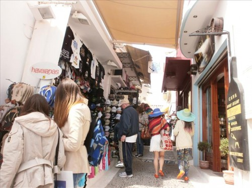 Tourists at a clothes stall in another narrow cobbled street.