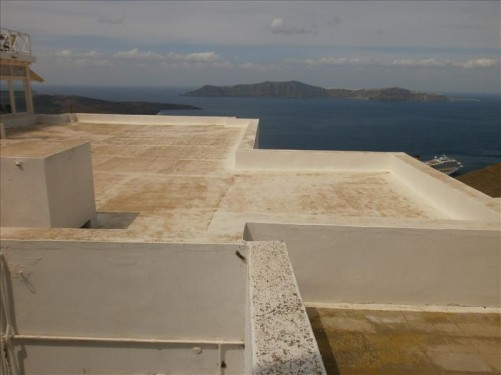 Looking from a white-painted flat roof top over the sea towards the island of Thirasia. Thirasia is part of the same small circular archipelago as Santorini. The archipelago is a volcanic caldera.