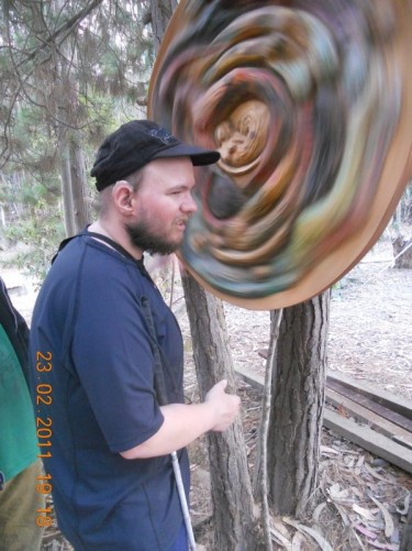Tony spinning a large wooden disc, which is attached to a tree.