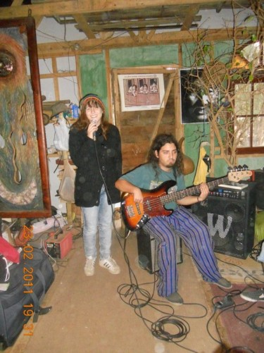 A teenage boy and girl: the girl is holding a microphone and the boy playing guitar.