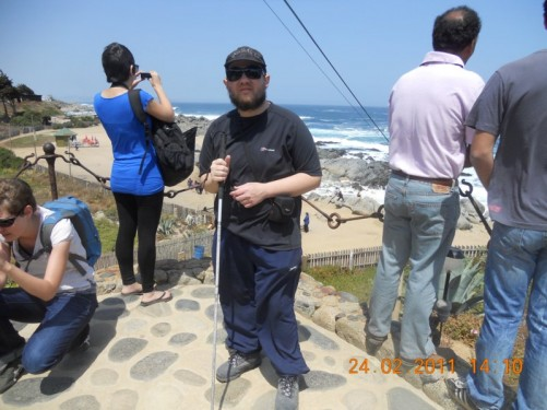 Tony with other visitors at a lookout point. The sandy beach, rocky shoreline, and the ocean beyond, can be seen.