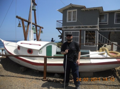 Tony in front of a white-painted wooden boat located immediately next to Pablo Neruda's house.