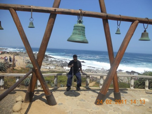Tony sitting on a wooden fence. The same bells as previously are in front. A large bell is in the centre with several smaller ones at either side. A good view across the beach below.