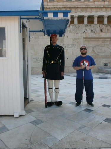 Tony next to a ceremonial guard. They are standing in front of the Tomb of the Unknown Soldier in Syntagma Square.