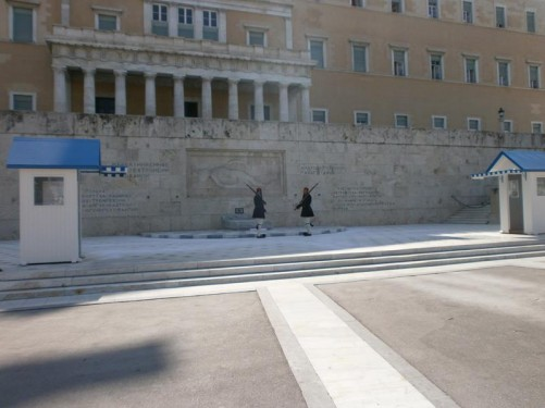Changing of the guard ceremony taking place in front of the Tomb of the Unknown Soldier. Two guards in traditional dress are standing facing each other. The guards are wearing red berets, black tunics, and also black pleated fustanellas, which are similar to kilts. They are carrying bayonets.