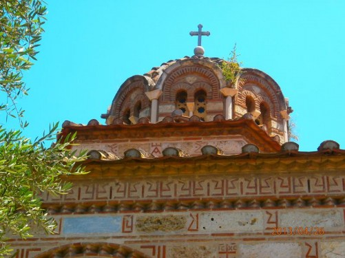 The church's dome from the outside. A cross on top. Decorative patterns along the walls.