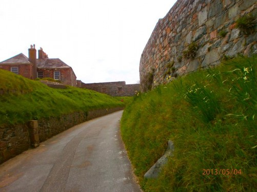 A path through the castle grounds. An early 19th century building on the left. This was originally a barracks hospital.