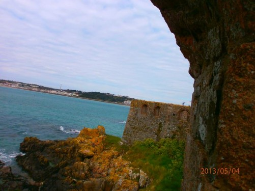 View along the defensive stone outer walls, with the rocky seashore below, and St Aubin's Bay beyond.