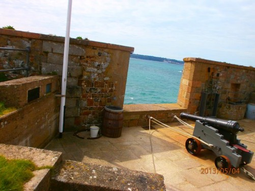 Another smaller type of canon pointing out to sea through a gap in the battlements.