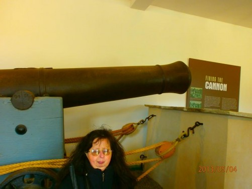 An historic canon inside a museum within the castle grounds. Tatiana in front.