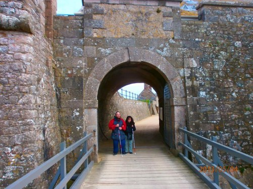 Tatiana and Tony standing inside a gate through the walls to the Lower Ward. A wooden bridge leading to the gate in front.