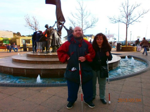 Tatiana and Tony in Liberation Square with the Liberation Sculpture behind them. The square and sculpture were created in 1995 to mark the 50th anniversary of Jersey's liberation from Nazi occupation. The sculpture depicts a group of islanders raising the Union Jack.