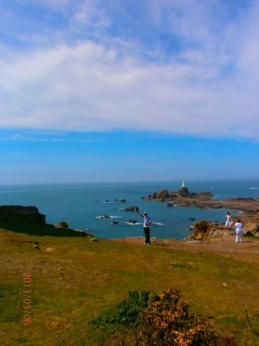 View from La Corbière: a headland located at the south-western point of Jersey in St Brelade. La Corbière lighthouse can be seen in the middle distance. It is built on a tidal island joined to the mainland by a causeway at low tide. The lighthouse tower is 19 metres (62 feet) high. It was lit for the first time on 24th April 1874.
