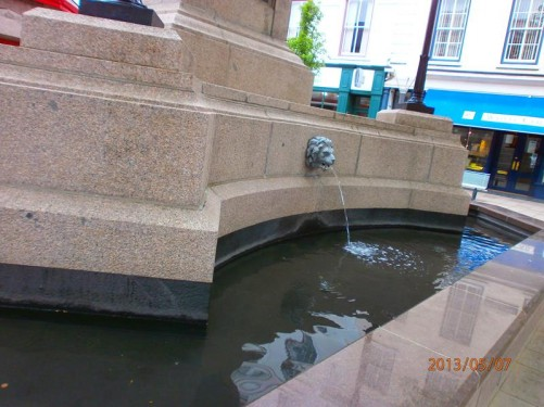 The same fountain: it includes a decorative lion's head with a stream of water coming out of the mouth.